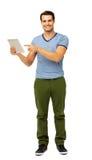 Porträt des gutaussehenden Mannes zeigend auf Digital-Tablet Stockbilder