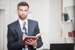 Porträt des hübschen überzeugten Geschäftsmannschreibens Lizenzfreie Stockfotografie