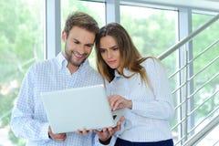 Porträt des hübschen überzeugten jungen Geschäftsmannes und jungen der Geschäftsfrau, die Computer, Lächeln, glücklich untersucht lizenzfreie stockbilder