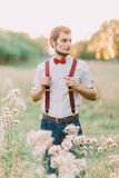 Porträt des hübschen überzeugten stilvollen Mannes, der auf dem Gebiet und den Blicken in den Abstand steht Lizenzfreie Stockfotografie