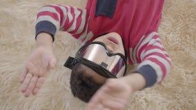 Porträt des hübschen Afroamerikanerjungen, der auf dem Boden auf dem beige flaumigen Teppich mit Skischutzbrillen auf seinen Au stock video footage