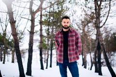 Porträt des hübschen bärtigen jungen Mannes in der roten Stellung des karierten Hemds im stilvollen Mann des Winters schneebedeck lizenzfreies stockfoto