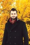 Porträt des hübschen bärtigen Mannes, der schwarzen Mantel im Herbst trägt Lizenzfreies Stockbild