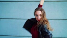 Porträt des hübschen Blondinetanzens gegen graue strukturierte Wand draußen stock footage