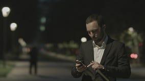 Porträt des hübschen erwachsenen Geschäftsmannes stehen telefonisch in der guten Laune, bei der Stellung in der Stadtstraße, Gesc Stockbilder