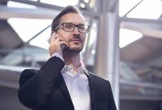 Porträt des hübschen Geschäftsmannes in der Klage und Brillen, die am Telefon im Flughafen sprechen Lizenzfreies Stockfoto