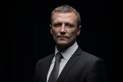 Porträt des hübschen Geschäftsmannes lokalisiert auf schwarzem Hintergrund Lizenzfreies Stockbild