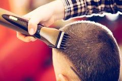 Porträt des hübschen jungen bärtigen kaukasischen Mannes, der modischen Haarschnitt im modernen Friseursalon erhält stockfoto