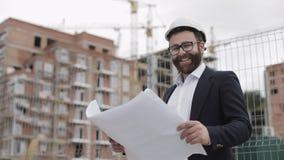 Porträt des hübschen jungen Ingenieurs auf der Baustelle, welche die Kamera betrachtet Der Erbauer mit Bauvorhabenständen stock video