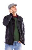 Porträt des hübschen jungen Mannes, der auf dem Telefon und dem Schauen spricht Stockfotos