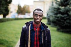 Porträt des hübschen jungen Mannes, der draußen draußen mit Straße der Tasche lächelt lizenzfreies stockbild
