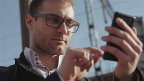 Porträt des hübschen jungen Mannes, der eine Textnachricht bei draußen stehen sendet stock video footage