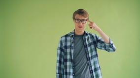 Porträt des hübschen jungen Mannes, der Finger am Tempel macht Kuckuckzeichen verdreht stock footage