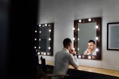 Porträt des hübschen jungen Mannes im weißen Hemd, das den Spiegel untersucht stockbild