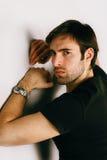 Porträt des hübschen Kerls in einem schwarzen T-Shirt und in einer Uhr auf einer Hand Stockfotos