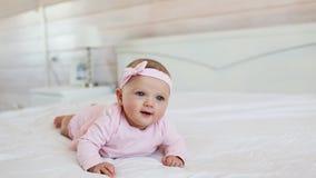 Porträt des hübschen Kindes im rosa Kleid auf einem Bett zu Hause stock video