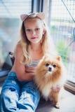 Porträt des hübschen kleinen Mädchens, das ihren Hund umarmt stockbild