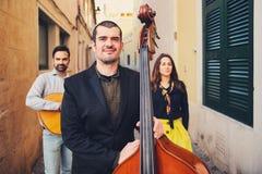 Porträt des hübschen lächelnden Mannes in einer alten Straße Im Hintergrund von zwei Musikern mit einer Gitarre und einem Sänger  Stockfoto