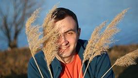 Porträt des hübschen lächelnden Mannes mit trockenem Gras, deckt im Freien mit Schilf stock video footage