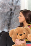 Porträt des hübschen Mädchens in der Strickjacke, die Spielzeug hält Stockfotografie