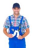 Porträt des hübschen männlichen Klempners, der Abflussrohr hält Stockfotografie
