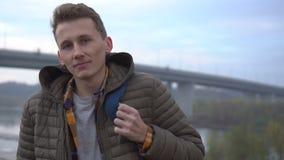 Porträt des hübschen netten kaukasischen Mannes im Freien Nahaufnahme Ernster junger Mann, der Kamera betrachtet stock video