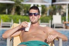 Porträt des hübschen trinkenden Safts des jungen Mannes auf dem Pool Stockfotografie