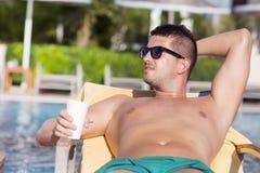 Porträt des hübschen trinkenden Safts des jungen Mannes auf dem Pool Lizenzfreie Stockfotografie