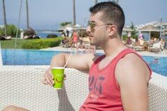 Porträt des hübschen trinkenden Safts des jungen Mannes auf dem Pool Stockfotos