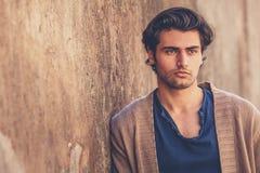 Porträt des hübschen und reizend jungen Mannes Er lehnt sich an einer Wand im Freien lizenzfreies stockbild