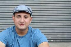 Porträt des hübschen wirklichen schauenden Mannes im Hut, der draußen sitzt lizenzfreie stockfotos