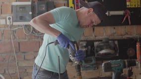 Porträt des Handwerkeringenieurs gerichtet auf die Bohrung eines Lochs mit Werkzeug auf dem Hintergrund einer kleinen Werkstatt K stock video