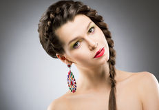 Porträt des hellen Brunette mit Schmuck - runder bunter Ohrring. Glänzendes Bijouterie Stockbilder