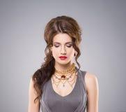 Porträt des herrlichen Brunette goldene LuxusKrone und Ohrringe tragend lizenzfreie stockfotografie