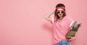 Porträt des Hippie-Mädchens in den Gläsern und in der Ananas auf rosa Hintergrund stockbilder
