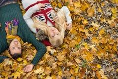 Porträt des hohen Winkels von den jungen Paaren, die auf Herbstlaub am Park liegen Lizenzfreie Stockfotos
