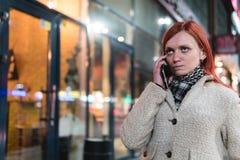 Porträt des Holdingmobiltelefons der jungen Frau in den Händen auf der Straße im Sommer, gereizten Ausdruck betrachtend, Ärger, I lizenzfreie stockfotos