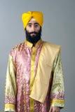 Porträt des indischen Sikhmannes mit dem buschigen Bart, der gegen einen grauen Hintergrund steht Stockbilder