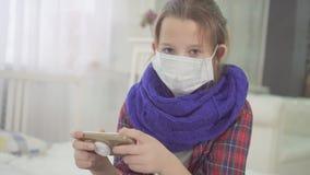 Porträt des jugendlich Mädchens mit der medizinischen Maske, welche die Kamera zu Hause sitzt auf Bett betrachtet stock footage