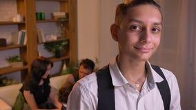 Porträt des jugendlichen arabischen Jungen, der direkt in Kamera mit bescheidenem Lächeln und seiner Familie auf Hintergrund aufp stock footage