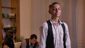 Porträt des jugendlichen entspannten arabischen Jungen, der direkt in Kamera mit bescheidenem Lächeln und seiner Familie auf Hint stock video