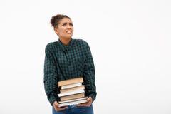 Porträt des jungen afrikanischen Mädchens mit Büchern über weißem Hintergrund Lizenzfreies Stockfoto