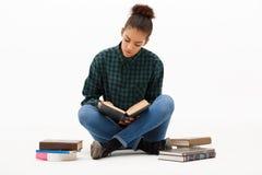 Porträt des jungen afrikanischen Mädchens mit Büchern über weißem Hintergrund Lizenzfreies Stockbild