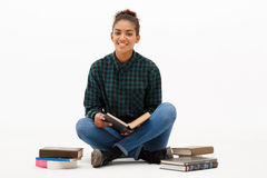 Porträt des jungen afrikanischen Mädchens mit Büchern über weißem Hintergrund Lizenzfreie Stockbilder