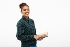 Porträt des jungen afrikanischen Mädchens mit Buch über weißem Hintergrund Lizenzfreie Stockfotos