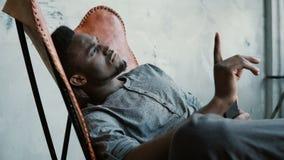 Porträt des jungen afrikanischen Mannes im Stuhl Mann ist ernsthaft denken und hält Smartphone Schreibenmitteilung des Kerls, läc Stockbild