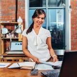 Porträt des jungen Anzeigenvertreters, der die Papiere stehen an ihrem Arbeitsplatz in der Agentur mit kreativem Innenraum hält Lizenzfreie Stockfotos