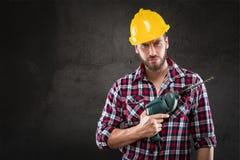 Porträt des jungen Arbeiters mit Bohrgerät stockfoto