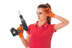 Porträt des jungen attraktiven Brunette Gebäude, dasfrau in der roten Uniform mit herein die Hände bohren, macht Erneuerung an lo stockfotografie