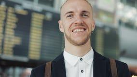 Porträt des jungen attraktiven Geschäftsmannes betrachtet in die Kamera dem Flughafen auf Abfahrt verschalt Hintergrund, glaubt stock video footage